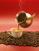 Turkish coffee is poured from a copper pot — Stock Photo