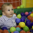 Toddler sitting in a basket of colored balls game — Stock Photo