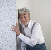 Smiling adult man leaning face to the white wall — Stock Photo
