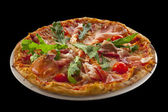 Pizza with arugula, cherry tomatoes, prosciutto isolated on blac — Stock Photo