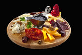 Platter of cheeses, sausages and nuts — Stock Photo