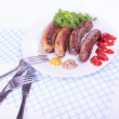Sausages on a plate with condiments — Stock Photo
