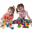 Two girls playing with colorful wooden designer sitting — Stock Photo