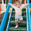 Happy little boy walking up on ladder — Stock Photo #34400143