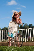 Girl with big hat and bicycle — Stock Photo