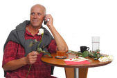 Mature man at the phone with a rose in is hand — Stock Photo