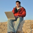 Young man with laptop on the beach — Stock Photo