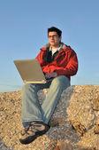 Mladý muž s notebookem na pláži — Stock fotografie