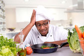 Desperate male chef with fruits and vegetables cooking — Stock Photo
