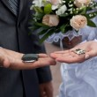 Couple's hands with lock, keys, and a wedding bouquet — Stock Photo