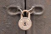 Old rusty padlock on a iron door  — Stock Photo