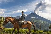Agricultor em um cavalo olhando para a erupção do vulcão tungurahua — Fotografia Stock