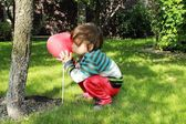 Little one with red heart balloon — Stockfoto