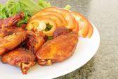 Kycklingvingar på en vit platta med grönsaker — Stockfoto