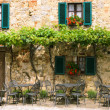 Cafe tables and chairs outside a stone building in Tuscany, Italy — Stock Photo #32200711