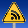 Yellow road hazard warning sign with RSS symbol on a sky background — Imagen vectorial