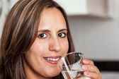 Woman smiling with a glass of water — Stock Photo