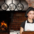 Woman Chef stand in the kitchen near wood oven — Stock Photo #23710767