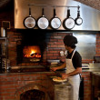 Pizza Chef put the pizza inside the Wood Oven — Stock Photo #23710769