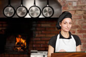 Woman Chef stand in the kitchen near wood oven — Stock Photo