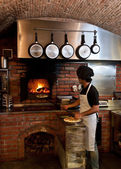 Pizza Chef put the pizza inside the Wood Oven — Stock Photo