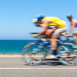 Cyclists competition along a coastal road — Stock Photo #26278429