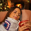 Woman having Hot Drink seating near Christmas Tree and Fireplace — Stock Photo