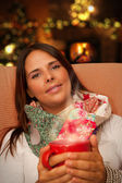 Woman holding Hot Drink seating near Christmas Tree and Fireplace — Stock Photo
