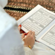 Foto Stock: Reading Koran