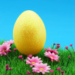 Stock Photo: Golden easter egg on flower meadow & nice intensely blue sky