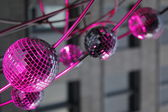 Pink lighted mirror christmas balls in city environment — Stock Photo
