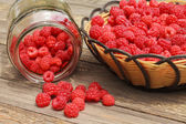 Raspberry still life with basket and glass jar on wooden table — Stock Photo