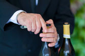 Waiter opening a bottle of white wine — Stock Photo