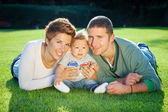 Family playing on grass — Stock Photo