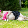 Pregnant woman lying in green grass — Stock Photo