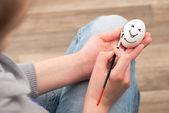 Girl draws on the egg. — Stock Photo