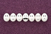 Seven eggs on purple sand. — Stock Photo