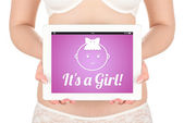 A pregnant woman is holding a tablet computer with the news about the child's gender girl. — Stockfoto