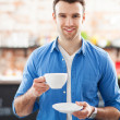 Waiter holding cups of coffee in cafe - Stock Photo