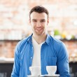 Stock Photo: Waiter holding cups of coffee in cafe