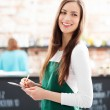 Young waitress holding notepad in cafe — Stock Photo #23639781