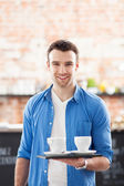 Waiter holding cups of coffee in cafe — Stock fotografie