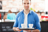 Waiter holding cups of coffee in cafe — ストック写真