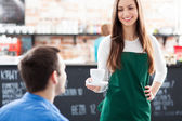 Waitress serving man coffee — Stock Photo