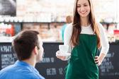 Waitress serving man coffee — Stock Photo