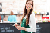Young waitress holding notepad in cafe — Stock Photo