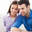 Young couple using laptop — Stockfoto