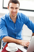 Young man using laptop in cafe — Stock Photo