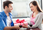 Man giving woman gift at cafe — Stock Photo