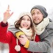 Young couple outdoors, woman pointing — Stock Photo